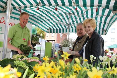 v.l. Hubertus und Edmund Lammers verkaufen einer Kundin auf dem Bürener Wochenmarkt ihre Blumen