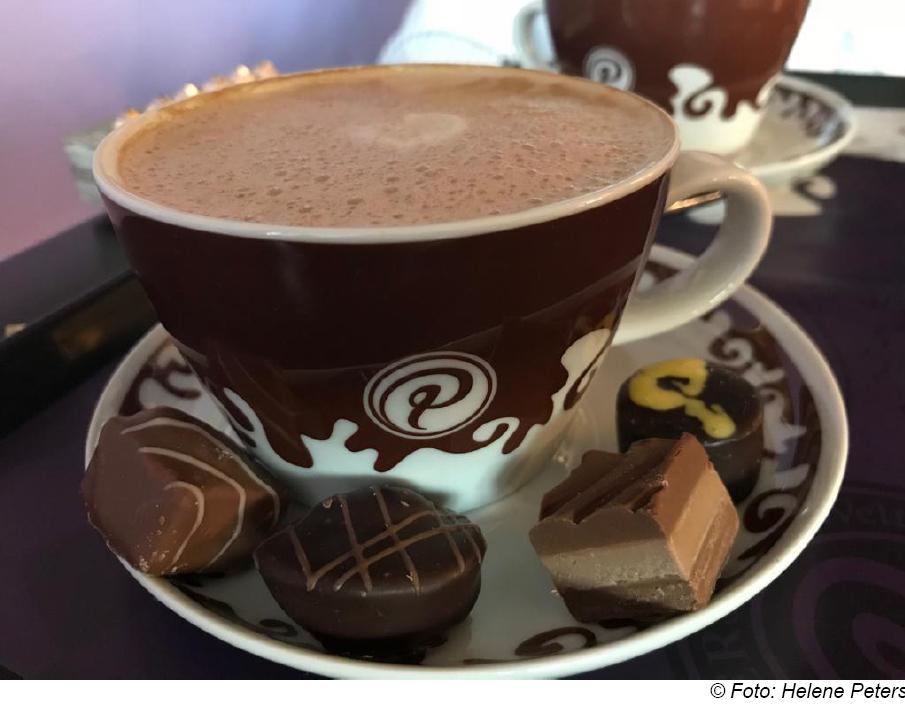 Kaffee mit vier Pralinen dekoriert.