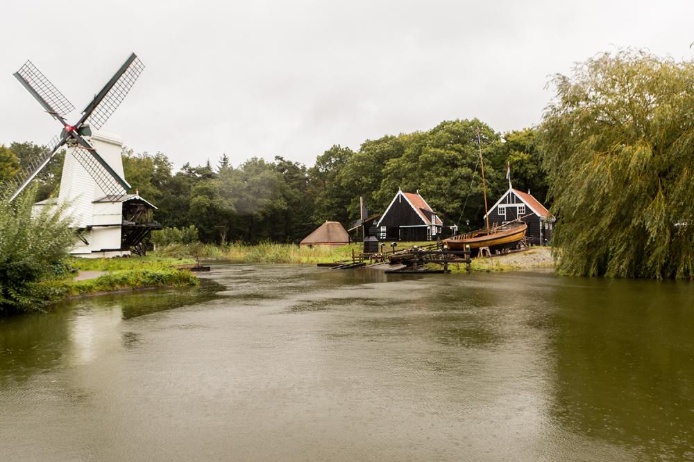 Links Windmühle, rechts zwei Häuser, in deren Hintergrund Wald und im Vordergrund Wasser.