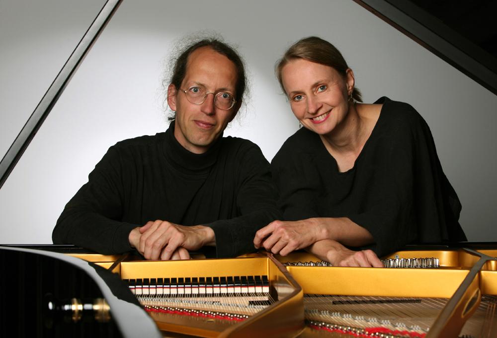 Mann und Frau posieren am Klavier.