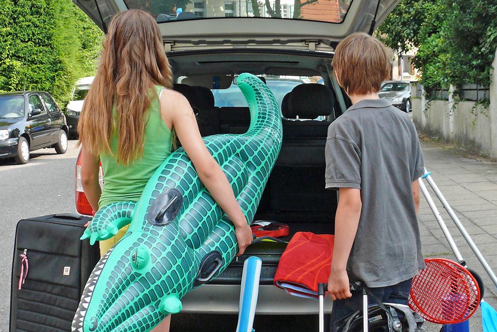 Zwei Kinder mit viel Gepäck stehen vor dem Kofferraum.