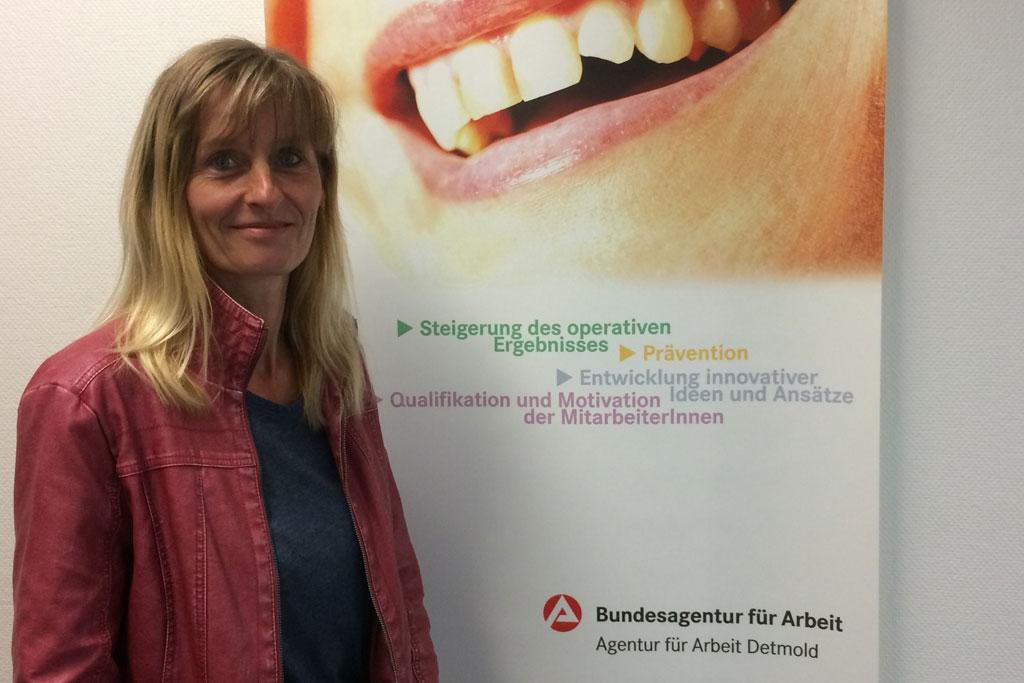 Bettina Kreiling vor einem Plakat.