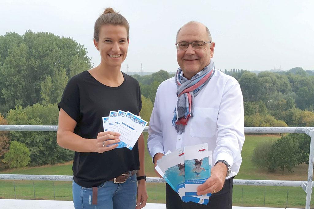 Birte Mai und Wolfgang Walter halten Flugblätter vor die Kamera.