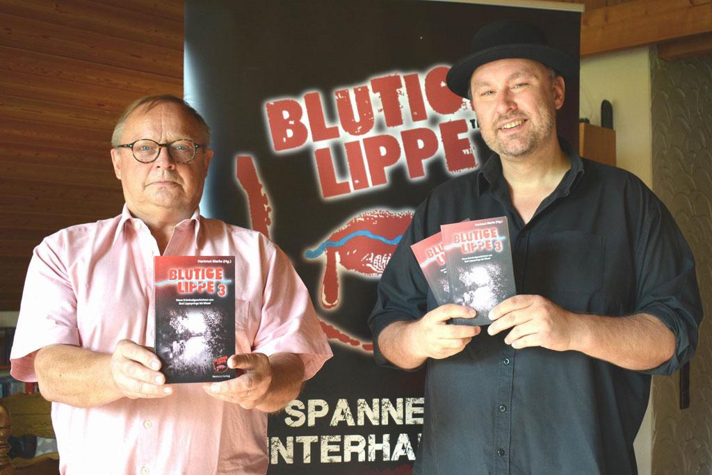 Zwei Männer halten Buch in die Kamera