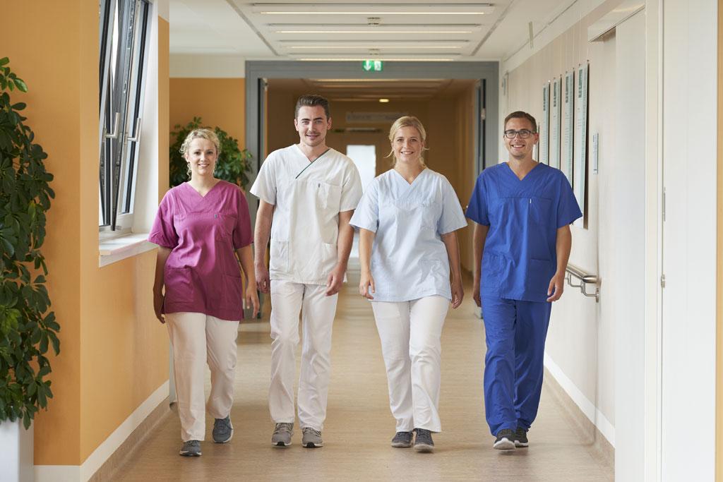 Vier junge Pfleger gehen durch den Flur.
