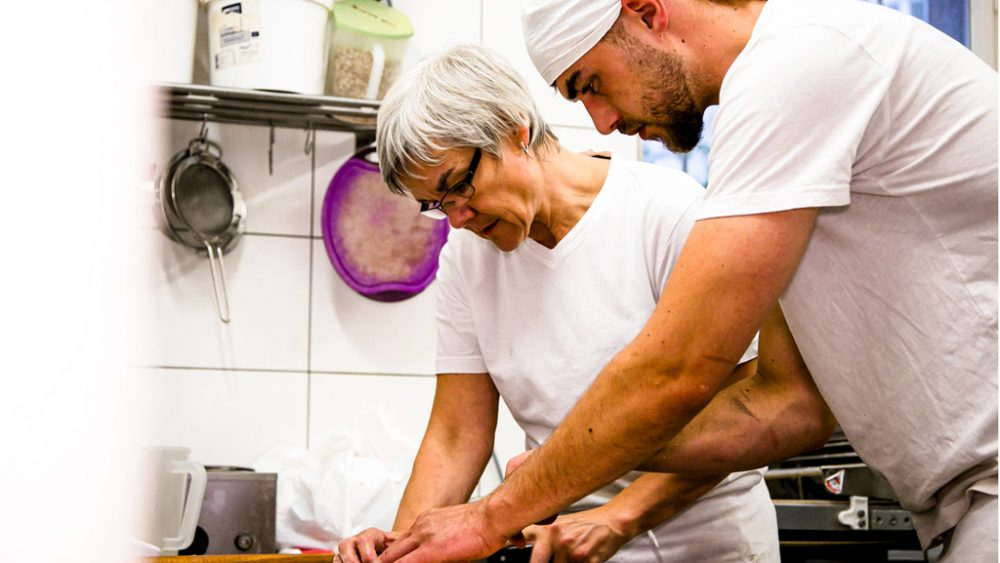 Zwei Menschen arbeiten in Bäckerei.