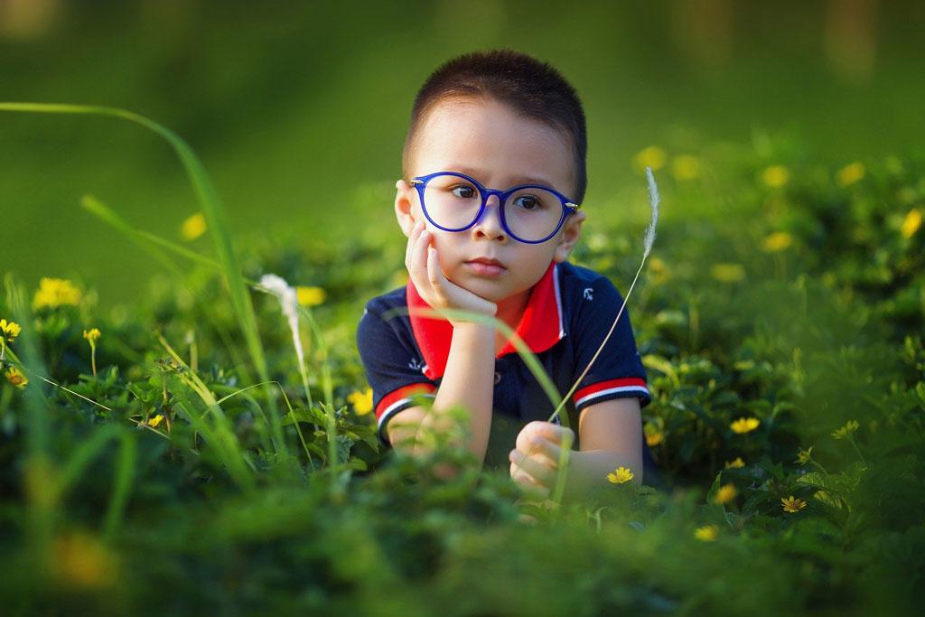 Junge liegt im Gras